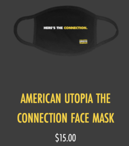 Black face mask with text that reads Here's the connection in white and yellow print. Text beneath the mask reads American Utopia The Connection Face Mask $15